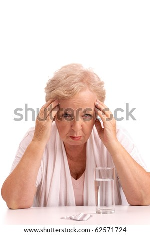 Portrait of sick aged woman touching head with tablets near by