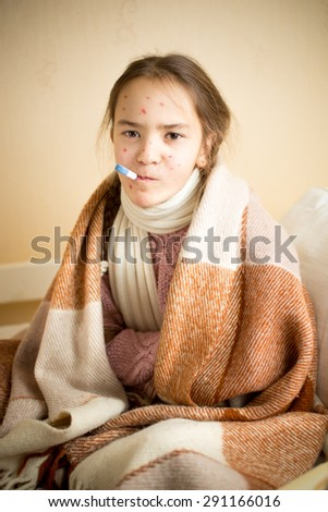 Portrait of sick girl with chickenpox measuring temperature with mouth thermometer - stock photo