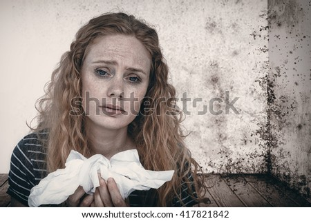 Portrait of sick woman holding paper tissue against image of a room corner