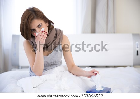 Portrait of sick woman on the bed at home - stock photo