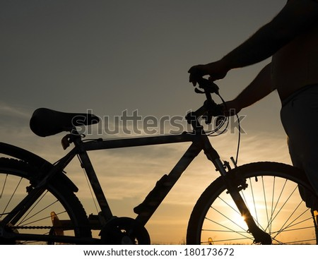 Portrait of silhouette of bicycle rider at sun set Young adult athlete man standing in summer field with cycle on sunset blue and yellow cloudy sky No face - stock photo