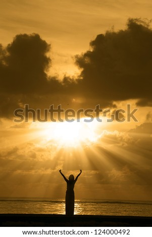 Portrait of silhouette of happy woman at beach. Shot during sunrise - stock photo