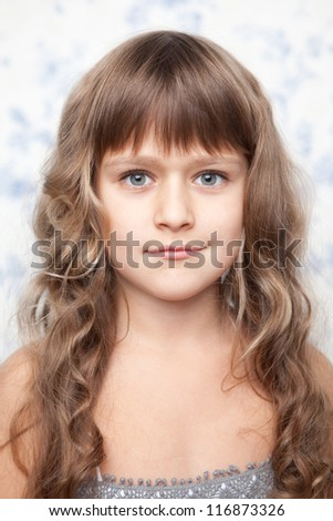 Portrait of sincere cheerful tender young blond girl child with grey eyes and wavy long hair looking at camera - stock photo
