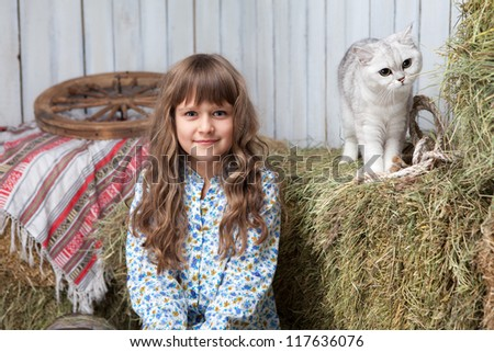 Portrait of sincere little blond girl villager and white cat on hay stack in wooden hayloft - stock photo