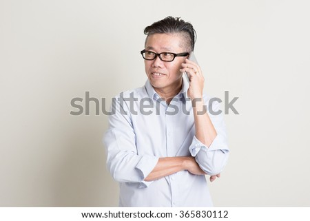 Portrait of single mature 50s Asian man in casual business calling on  smartphone and smiling, standing over plain background with shadow. Chinese senior male people. - stock photo