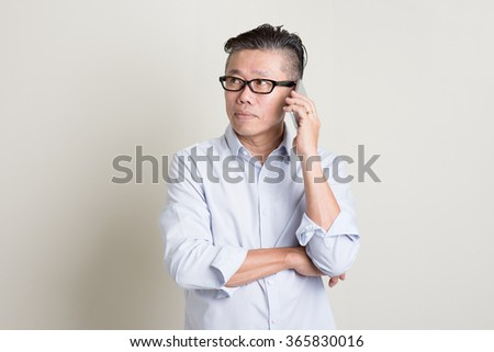 Portrait of single mature 50s Asian man in casual business calling on  smartphone, standing over plain background with shadow. Chinese senior male people.