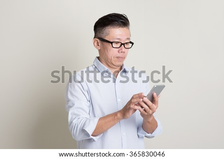 Portrait of single mature 50s Asian man in casual business playing smartphone, standing over plain background with shadow. Chinese senior male people. - stock photo
