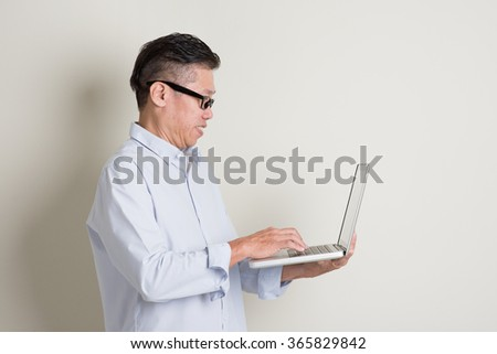 Portrait of single mature 50s Asian man in casual business using notebook computer and smiling, standing over plain background with shadow. Chinese senior male people. - stock photo