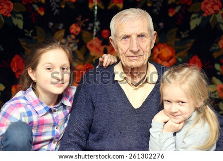 portrait of  sitting senior man and  granddaughters at home