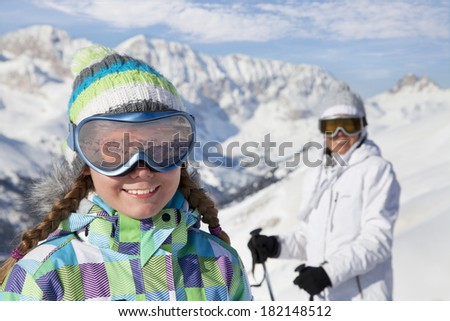 Portrait of skiers, mother and daughter, on ski slope in Italian Dolomites  - stock photo