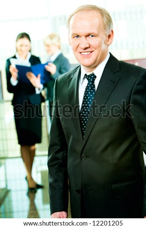 Portrait of skilful manager standing in the office on the background of business women - stock photo