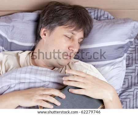 Portrait of sleeping man with book in bed