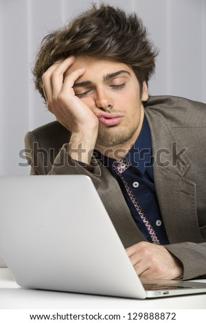 Portrait of sleeping overworked businessman in front of his laptop at work. - stock photo