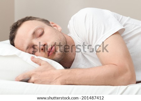 Portrait of sleeping Young Caucasian man in white - stock photo