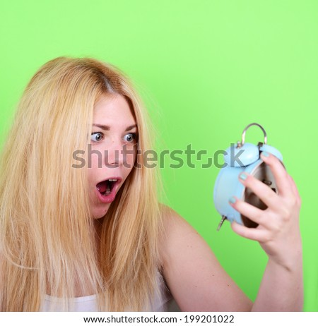 Portrait of sleepy young female in chaos holding clock against green background - Running late concept - stock photo