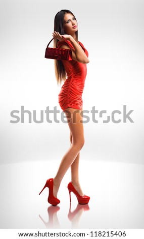 Portrait of slender  long legged brunette beauty in little red dress. - stock photo