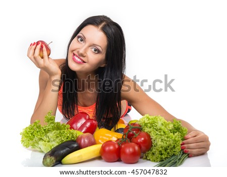 Portrait of slim fitness cheerful girl lying in studio with set of fruit and vegetables over white background. Healthy eating, diet, fitness, weight lose concept.