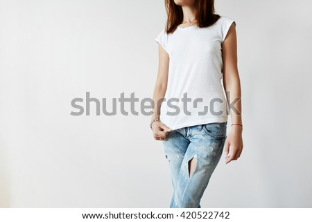 Portrait of slim young woman with dark hair wearing white T-shirt and blue ripped jeans after having physical activity in gym. Hipster girl standing isolated against white stduio wall background - stock photo