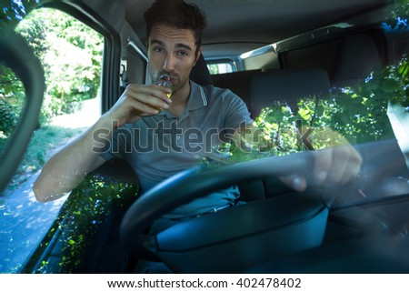Portrait of slumped man drinking alcohol while driving car - stock photo