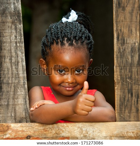 Portrait of small african girl doing thumbs up at wooden fence. - stock photo