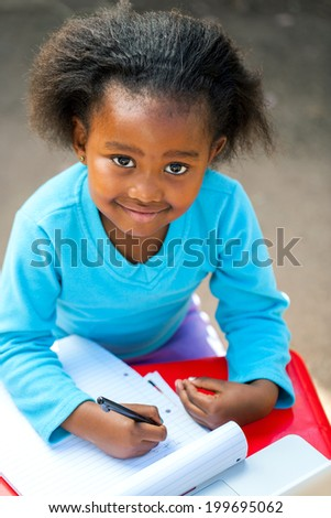 Portrait of small African kid writing in notebook at desk. - stock photo
