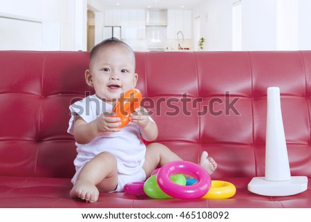 Portrait of small baby sitting on the red couch and playing a pyramid toy at home