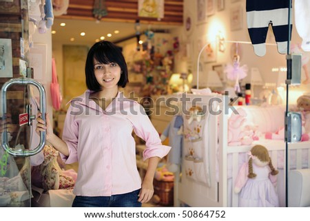 portrait of small business owner: proud woman opening her baby store - stock photo