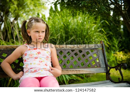 Portrait of small offended child - outdoor in backyard - stock photo
