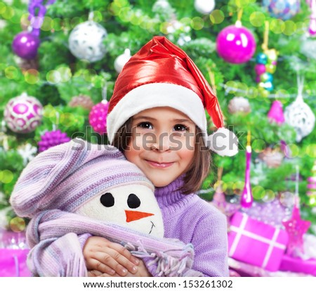 Portrait of small pretty girl wearing red santa hat hugging soft toy of white snowman over Christmas tree, New Year child's party - stock photo