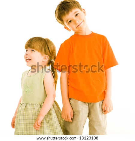 Portrait of small sister and brother standing next to each other over white background - stock photo