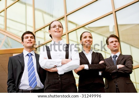 Portrait of smart associates standing in row and looking forwards with successful woman in front - stock photo