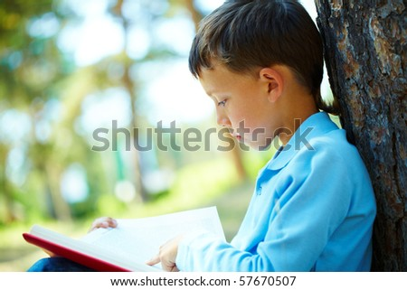 Portrait of smart boy sitting by tree trunk in the park and reading book - stock photo