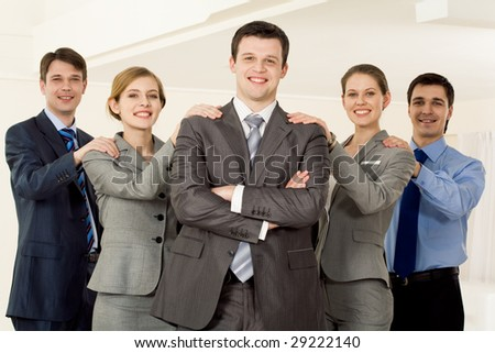 Portrait of smart business people keeping their hands on each others? shoulders and looking at camera with confident leader at foreground - stock photo