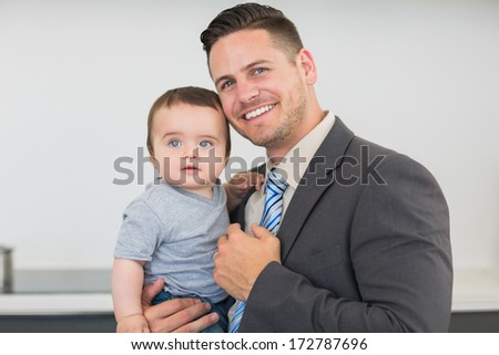 Portrait of smart businessman carrying baby boy in kitchen at home - stock photo