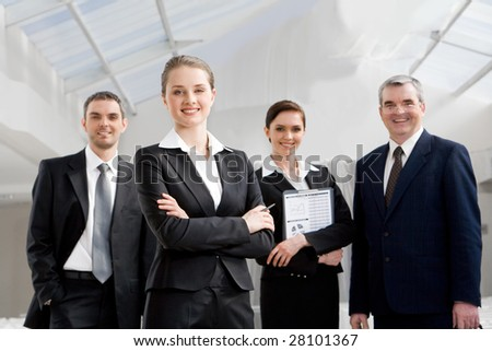 Portrait of smart businesswoman looking at camera at background of co-workers - stock photo