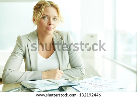 Portrait of smart businesswoman looking at camera at workplace - stock photo