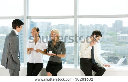 Portrait of smart businesswomen having a cup of coffee and speaking to confident employee with typing partner near by - stock photo