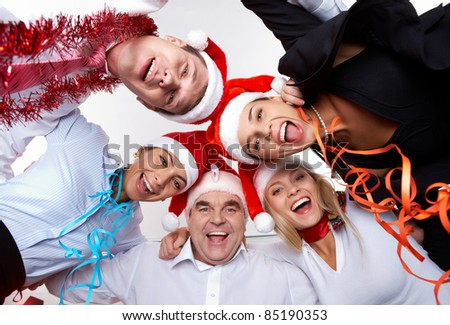Portrait of smart colleagues in Santa caps wishing you Merry Christmas - stock photo