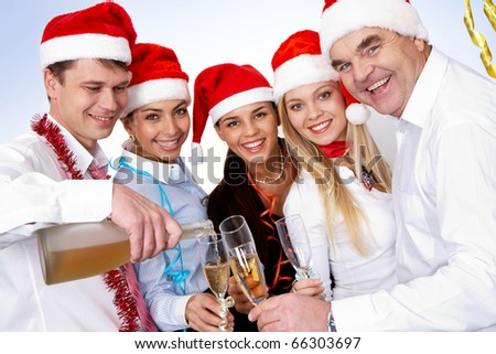 Portrait of smart colleagues with flutes of champagne looking at camera - stock photo