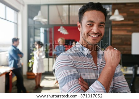 Portrait of smart creative professional looking at camera and smiling. Happy caucasian man standing in office with coworkers discussing in office. - stock photo