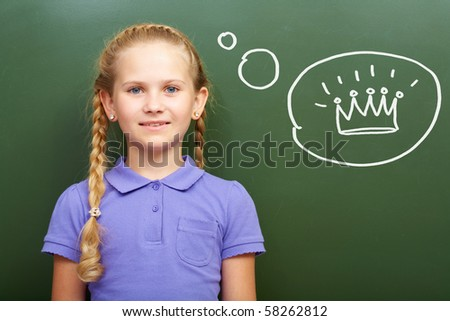 Portrait of smart girl by the blackboard thinking of crown and looking at camera - stock photo