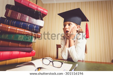 Portrait of smart girl in graduation cap looking at high heap of books on table at library - stock photo