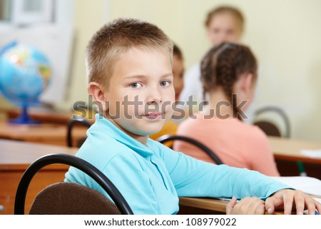 Portrait of smart lad at workplace with classmates and teacher on background - stock photo