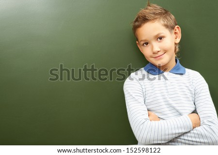Portrait of smart lad by the blackboard looking at camera - stock photo