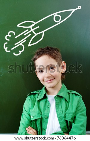Portrait of smart lad by the blackboard thinking of airplane and looking at camera - stock photo