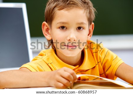 Portrait of smart lad looking at camera during reading lesson - stock photo