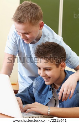 Portrait of smart lads working with laptop during lesson