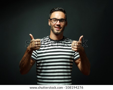 Portrait of smart man in glasses smiling and giving you two thumbs up on black background - stock photo