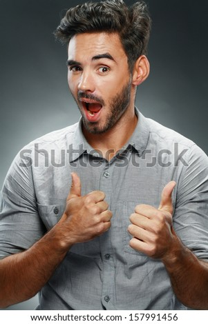 Portrait of smart man smiling and show giving you two thumbs up on dark studio background - stock photo