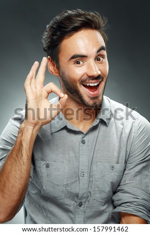 Portrait of smart man smiling and show ok sigh on dark studio background - stock photo